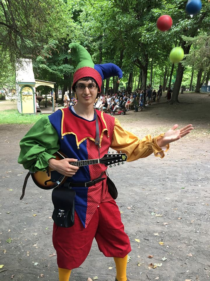 (Picture of Josh at a Renaissance Faire holding a mandolin and juggling)